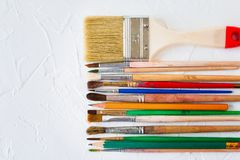 Paint brushes of different sizes and pencils on white texture background. Art and education object stock image
