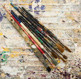 Paint brushes on dried paint background Royalty Free Stock Images
