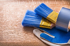 Paint brushes in duct tape on protective gloves Royalty Free Stock Photos