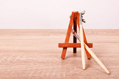 Paint brushes and an easel. A close up shot of paint brushes and an easel on a wooden table Royalty Free Stock Photo