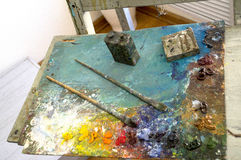 Paint, brushes and easel painter Stock Photography