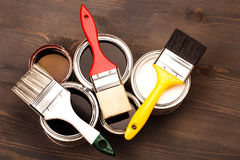 Paint brushes on five cans. Multicolor paint brushes on five cans lying on wooden clean grew textured table. Top view Royalty Free Stock Photography