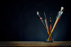 Paint brushes in a glass. Black background Stock Image