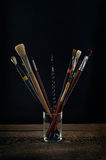 Paint brushes in a glass. Black background Stock Images