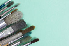 Paint brushes. On a green paper Stock Photos