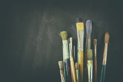 Paint brushes in jar over blackboard background stock images