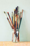 Paint brushes in jar over wooden aqua blue background Stock Image