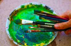 Paint brushes in man hand to the painting palette Stock Photos