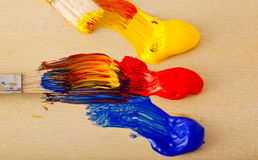 Paint brushes and oils. Brushes streaking paint in primary colors Royalty Free Stock Images