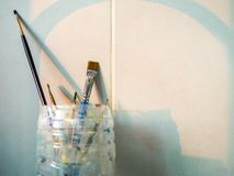 Paint brushes in old plastic cup. With copy space stock photo