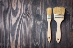 Paint brushes on old wooden background Stock Photos