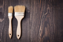Paint brushes on old wooden background Royalty Free Stock Photos