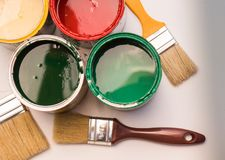 Paint brushes and opened paint cans Stock Photos