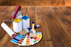 Paint brushes and paint cans for repair on wooden. Paint brushes cans measuring tape wooden background color colors stock images