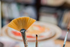 Paint brushes in a painting workshop. With a colorful background inspiring creation Royalty Free Stock Photography