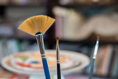 Paint brushes in a painting workshop. With a colorful background inspiring creation Stock Photos