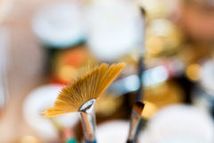 Paint brushes in a painting workshop. With a colorful background inspiring creation Royalty Free Stock Image
