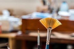 Paint brushes in a painting workshop Stock Photos