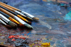 Paint brushes on a palette. Paint brushes on a palette close up Royalty Free Stock Images