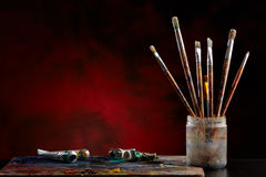 Paint brushes with a palette. Paint brushes with a palette on a colored background Stock Image