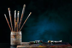 Paint brushes with a palette. Paint brushes with a palette on a colored background Stock Images