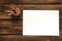Paint brushes and paper on wooden background. With space for your text stock photo