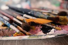 Paint Brushes Placed on the Color Palette , Macro Shot with Blurred  Background royalty free stock photography