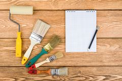 Paint brushes, roller and notepad stock image