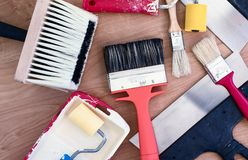 Paint brushes, rollers and putty knifes on a wooden background stock photo