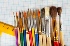 Paint brushes and ruler on checkered paper background Royalty Free Stock Photo