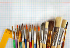 Paint brushes and ruler on checkered paper background Royalty Free Stock Images