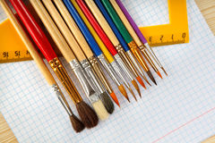 Paint brushes, ruler and checkered paper on wooden background Stock Photography