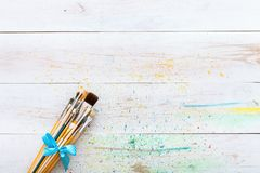 Paint brushes set on white wooden painted stained table with splashes, artistic canvas background, creative space for painting, stock images