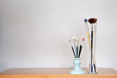Paint Brushes. On shelf in front of blank wall royalty free stock image