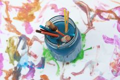 Paint brushes soaking in a glass jar of soapy water Royalty Free Stock Photo