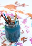 Paint brushes soaking in a glass jar of soapy water Stock Image