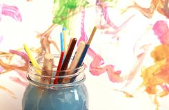 Paint brushes soaking in a glass jar of soapy water Royalty Free Stock Photography