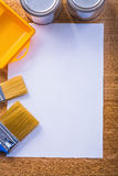 Paint brushes tray cans sheet of paper Stock Image
