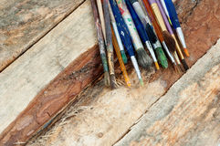 Paint brushes. Used artist paint brushes on a rough wooden surface stock photography
