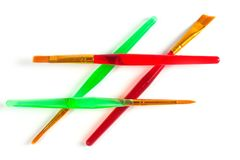 Paint brushes of various shapes and widths with bright plastic handles.  stock illustration
