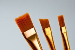 Paint brushes of various shapes and widths with bright plastic handles.  royalty free illustration