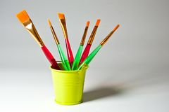 Paint brushes of various shapes and widths with bright plastic handles.  vector illustration