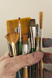 Paint brushes. Of various sizes in a mans hand Royalty Free Stock Images