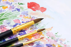 Paint brushes on watercolor backdrop. Set of paint brushes on hand watercolor background Royalty Free Stock Photos