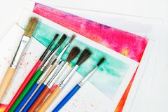 Paint brushes on watercolor drawings. Paint brushes are on watercolor drawings on the table on a white background, top view stock photos