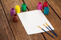 Paint brushes, watercolor paints and white paper Stock Image