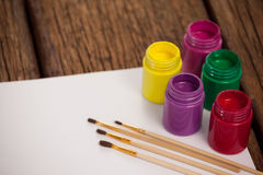 Paint brushes, watercolor paints and white paper Stock Photography