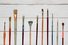 Paint brushes on a white wooden background, top view Royalty Free Stock Photography