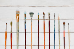 Paint brushes on a white wooden background, top view. Different brushes to paint on a white wooden background, top view Royalty Free Stock Images