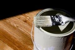 Paint Bucket on Hardwood Floor. With Paintbrush Stock Photo